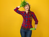 Smiling modern woman grower using fresh parsley as an accessory. Healthy food to your table. Portrait of smiling modern woman grower in checkered shirt on yellow Royalty Free Stock Photo