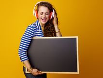 Smiling modern woman in headphones looking at blank board Stock Photography