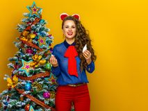 Smiling modern woman near Christmas tree holding nasal spray Royalty Free Stock Images