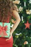 Smiling modern woman hiding green Christmas gift behind back stock photo