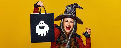 Smiling modern woman showing shopping bag and frightening. Colorful halloween. smiling modern woman in halloween witch costume isolated on yellow background royalty free stock image