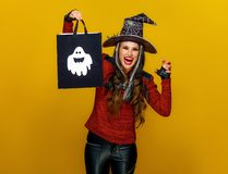 Smiling modern woman showing shopping bag and frightening. Colorful halloween. smiling modern woman in halloween witch costume isolated on yellow background stock photo