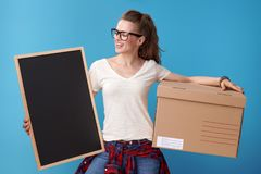 Smiling woman with cardboard box looking at blank board on blue Stock Photography
