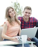 Modern young people using laptop at home. Smiling modern young people using laptop at home Stock Photos