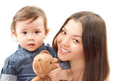 Smiling mom and baby girl with toy bear Royalty Free Stock Photo