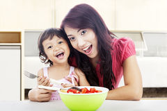 Smiling mom and daughter in kitchen Royalty Free Stock Images