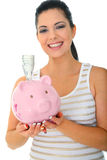 Smiling Mom Holding Piggy Bank. Save money concept. a woman holding pink piggybank and inserting money inside. isolated stock image