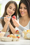 Smiling mom painting Easter eggs with daughter Stock Image