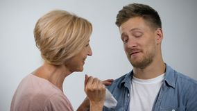 Smiling mom wiping mouth to infantile adult son, overprotection effect concept. Stock footage stock video