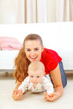 Smiling mommy and adorable baby playing on floor Stock Photo