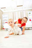 Smiling mommy playing with creeping on floor baby Stock Photos