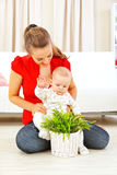 Smiling mommy showing plant to her baby Royalty Free Stock Image
