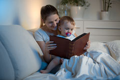 Smiling mother and adorable baby reading book before going to sl Royalty Free Stock Photography