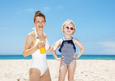 Smiling mother applying sunscreen on daughters arm at beach Stock Images