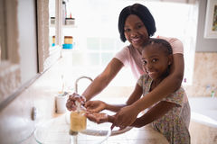 Smiling mother assisting daughter while washing hands in bathroom at home stock photography