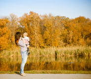 Smiling mother and baby on autumn lake Stock Photography