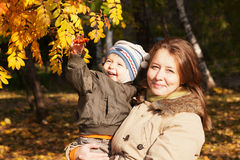 Smiling mother with a baby on autumn walk Royalty Free Stock Photo