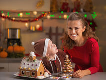 Smiling mother and baby with christmas cookie house in kitchen Royalty Free Stock Image
