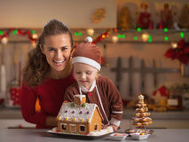 Smiling mother and baby decorating christmas cookie house Royalty Free Stock Photo
