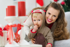 Smiling mother and baby eating Christmas cookie Royalty Free Stock Photos
