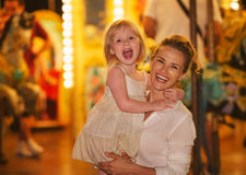 Smiling mother and baby girl in front of carousel Royalty Free Stock Photos
