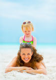Smiling mother and baby girl playing on beach Stock Image