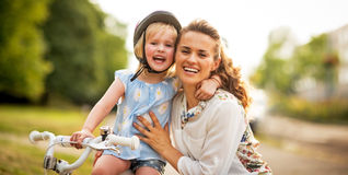 Smiling mother and baby girl sitting on bicycle Royalty Free Stock Photo