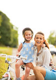 Smiling mother and baby girl sitting on bicycle Royalty Free Stock Image