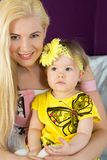 Smiling mother with baby on her lap. In dress with butterfly stock photo