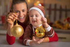 Smiling mother and baby holding christmas balls Stock Image