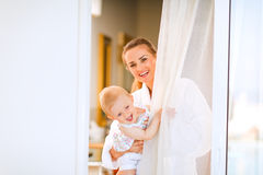Smiling mother with baby looking out  from window Stock Images