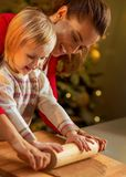 Mother and baby rolling pin dough in christmas decorated Stock Photo