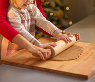 Smiling mother and baby rolling pin dough in kitchen Stock Photography