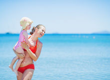 Smiling mother and baby on sea background looking on copy space. High-resolution photo royalty free stock photography