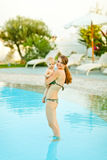 Smiling mother with baby standing in swimming pool Stock Photography