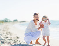 Smiling mother and baby wearing sunglasses on beach Royalty Free Stock Photo