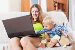 Smiling mother with baby working online Stock Photography