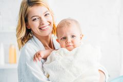 Smiling mother in bathrobe holding little child. Covered with towel and looking at camera stock photos