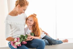 Mother with flowers hugging little daughter Stock Photo