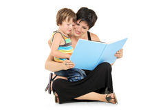 Smiling mother and boy reading a book together. Isolated on white background Royalty Free Stock Photo