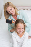 Smiling mother brushing her daughters hair. In the bedroom royalty free stock photo