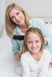 Smiling mother brushing her daughters hair. In the bedroom stock photography