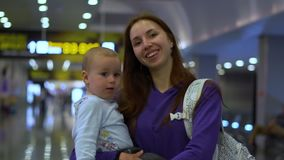 Smiling mother carries a beautiful baby around the airport in slow motion. Smiling mother carries a beautiful small baby and shows an OK gesture. They walk along stock footage