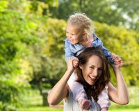 Smiling mother carrying cute little girl on shoulders Royalty Free Stock Image