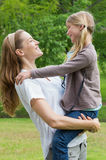 Smiling mother carrying daughter at park Stock Images