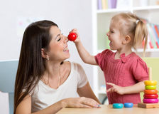 Smiling mother and child daughter in the nursery, happy time and togetherness Stock Photos