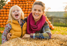 Smiling mother and child near haystack Stock Photo