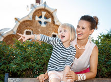Smiling mother and child pointing on something in Park Guell Stock Image