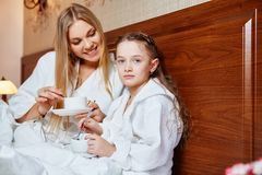 Smiling mother and child resting in bed after Spa treatments. Th royalty free stock image