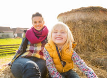Smiling mother and child sitting on haystack Stock Photography